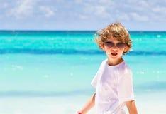在热带海滩的小男孩佩带的太阳镜 库存图片