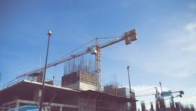 大厦起重机和建造场所在蓝天下 免版税库存图片