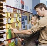 Επιχειρηματίες που διαβάζουν τις υπενθυμίσεις στον πίνακα δελτίων στην αρχή Στοκ Εικόνες