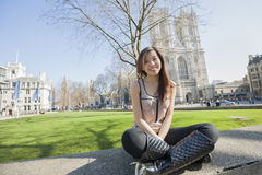 Полнометражный портрет молодой женщины сидя против Вестминстерского Аббатства в Лондоне, Англии, Великобритании Стоковая Фотография RF