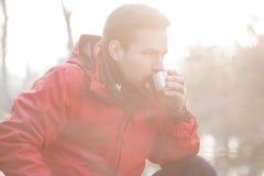 男性远足者饮用的咖啡在森林里 库存照片