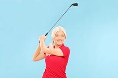 摇摆高尔夫俱乐部的女性高尔夫球运动员 库存照片