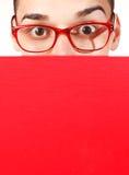 Κατάπληκτος σπουδαστής με το κόκκινο σημειωματάριο και τα κόκκινα γυαλιά Στοκ φωτογραφία με δικαίωμα ελεύθερης χρήσης