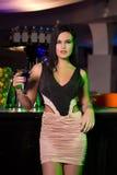 拿着在酒吧的深色的妇女鸡尾酒 免版税库存照片