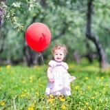 有一个红色气球的滑稽的女婴在庭院里 图库摄影