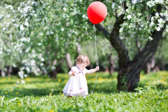 滑稽的女婴在有红色轻快优雅的苹果树庭院里 免版税库存照片