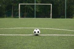踢的足球经典黑白球在运动场 免版税库存图片