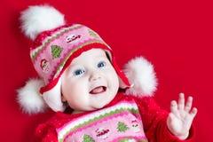 圣诞节的愉快的笑的女婴编织了帽子 库存照片