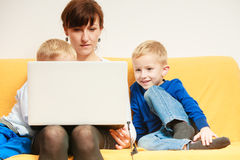 愉快的系列 使用膝上型计算机的母亲和儿子在家坐沙发 免版税库存照片