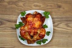 新鲜的烤箱烤整鸡用在服务板材的荷兰芹 图库摄影