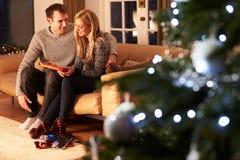 交换礼物的夫妇由圣诞树 图库摄影