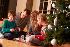 解开礼物的家庭由圣诞树 免版税图库摄影