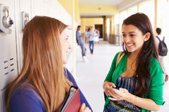 Δύο θηλυκοί σπουδαστές γυμνασίου που μιλούν από τα ντουλάπια Στοκ Φωτογραφίες