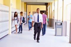 Студенты и учитель средней школы идя вдоль прихожей Стоковая Фотография RF