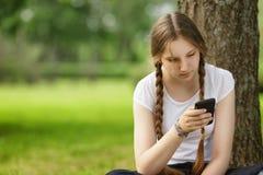 坐在与手机的树附近的青少年的女孩 免版税图库摄影
