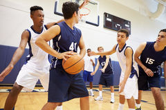 打比赛的男性高中蓝球队 免版税图库摄影