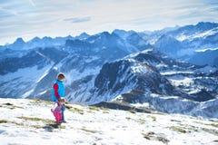 Ευτυχές αγόρι με την αδελφή μωρών του στα βουνά χιονιού Στοκ Φωτογραφίες