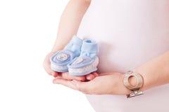 拿着对婴孩的蓝色鞋子的孕妇 免版税库存照片