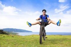 骑自行车的滑稽的年轻背包徒步旅行者在草甸 免版税库存图片