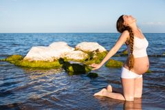 做在放松的体育胸罩的孕妇锻炼在海的瑜伽姿势 库存照片