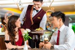 中国侍者服务晚餐在典雅的餐馆或旅馆 免版税图库摄影