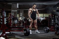 Человек культуриста стоя с штангой, разминкой в спортзале Стоковые Фотографии RF