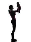 拿着婴孩剪影的妇女母亲 图库摄影