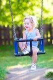 在操场的甜笑的小孩女孩摇摆的乘驾 库存照片