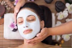 少妇的温泉疗法有面部面具在美容院 库存照片