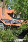 有太阳电池板的现代红色铺磁砖的遮阳篷顶 免版税图库摄影