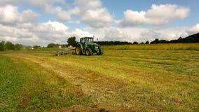 大收割机在干草,有运作在草甸的干草制造商的卡车上转动在农田里 股票录像