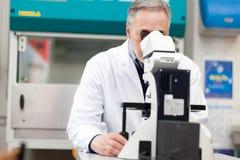 看通过显微镜的男性科学家 库存照片