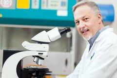 看通过显微镜的科学家举办的研究 免版税库存图片