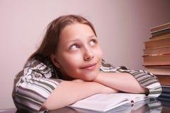 坐与书的愉快的青少年的女孩 库存图片