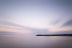 在日落的惊人的长的曝光风景灯塔与安静 库存照片