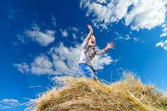 小男孩尖叫在堆干草反对蓝天在一个晴天 免版税库存图片