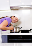 弯曲在火炉的一个罐的微笑的厨师 免版税图库摄影
