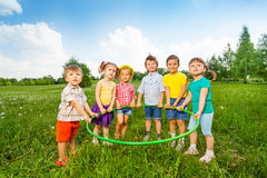 结合在一起使一个箍的六个滑稽的孩子 免版税图库摄影