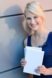 有外面书的微笑的白肤金发的学生女孩 库存图片