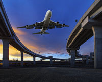 Το αεροπλάνο επιβατικών αεροπλάνων που πετά πέρα από τη γέφυρα εδάφους μεταφορών χρησιμοποιεί αυτήν την εικόνα για το θέμα μεταφο Στοκ Φωτογραφία