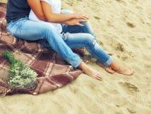 在牛仔裤、男人和妇女的腿坐在沙子的格子花呢披肩毯子在海滩 免版税库存图片