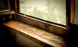 在倾吐的雨下的老木窗口基石 免版税图库摄影