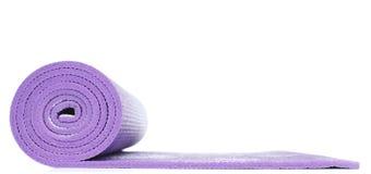 紫罗兰色瑜伽席子在白色背景中 库存照片