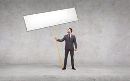 Χαμογελώντας επιχειρηματίας που κρατά το λευκό κενό χαρτόνι Στοκ Φωτογραφία