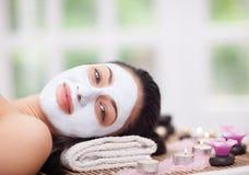 少妇的温泉疗法有面部面具在美容院 库存图片
