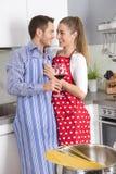 年轻新已婚夫妇在一起烹调面团的厨房里 免版税库存照片