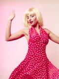 白肤金发的假发和减速火箭的红色礼服跳舞的美丽的画报女孩 当事人 图库摄影