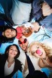 小组圈子的愉快的青年人在蓝天背景 免版税库存照片
