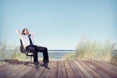放松在办公室椅子的商人在海滩 库存图片