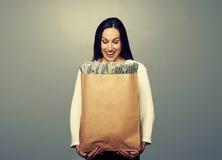 拿着纸袋的兴高采烈的女实业家 免版税库存图片